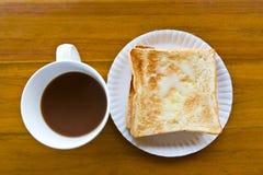 De kop van de koffie en giet de melktoost Stock Foto's