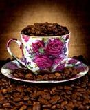 De kop van de koffie en het vierkant van koffiebonen stock afbeeldingen
