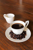De kop van de koffie met de Bonen van de Koffie en melk op grunge wo Stock Fotografie