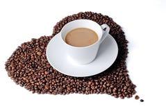 De kop van de koffie met hart gevormde koffiebonen Stock Afbeeldingen