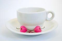 De kop van de koffie met het aftappen van hartbloem Stock Foto