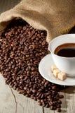 De kop van de koffie met jutezak van geroosterde bonen Royalty-vrije Stock Foto