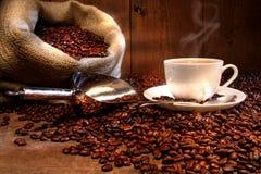 De kop van de koffie met jutezak van geroosterde bonen