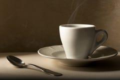 De Kop van de koffie met Lepel op Beige royalty-vrije stock afbeelding