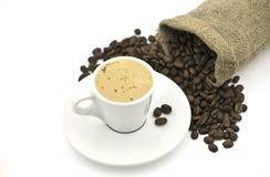 De Kop van de koffie naast de Bonen van de Koffie Stock Afbeeldingen