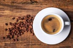 De kop van de koffie op een houten lijst Donkere achtergrond Stock Afbeeldingen