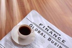 De kop van de koffie op een krant stock afbeeldingen