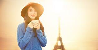 De kop van de meisjesholding van koffie op de torenachtergrond van Eiffel Stock Afbeelding