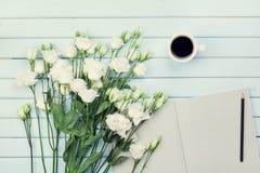 De kop van de ochtendkoffie, lege document lijst, potlood, en boeket van witte bloemeneustoma op blauwe rustieke lijst luchtmenin Royalty-vrije Stock Foto