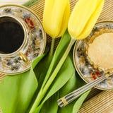 De kop van de porseleinkoffie met gele tulpenbloemen en cake Royalty-vrije Stock Foto's
