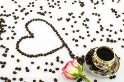 De kop van de porseleinkoffie met roze bloem en koffiebonenhart Royalty-vrije Stock Afbeeldingen