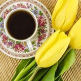 De kop van de porseleinthee met gele tulpenbloemen Royalty-vrije Stock Afbeelding