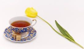 De kop van de thee met tulp stock afbeeldingen