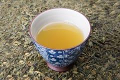 De kop van de thee op thee doorbladert stock foto's