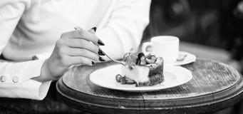 De kop van de dessertcake van koffie en vrouwelijke hand met vork dichte omhooggaand Stuk van cake met rode bes Gastronomisch rec royalty-vrije stock foto