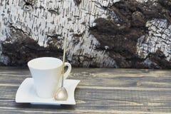 De kop van het koffieporselein en schotel van witte kleur en zilveren lepel met verdraaid handvat tegen achtergrond van berkescho stock afbeelding