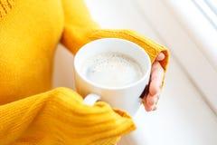 De kop van hete koffie met melk in uw handen Drankconcept, Stock Foto