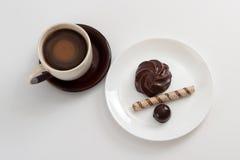 De kop van koffie en chocoladesuikergoed, de heemst en het wafeltje rollen op plaat stock afbeeldingen
