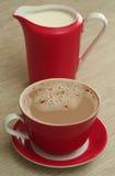 De kop van koffie en de melk zijn op een lijst Stock Foto
