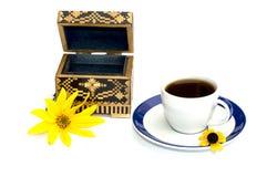 De kop van koffie en kist met een gele bloem, ISO wordt verfraaid die Stock Foto's