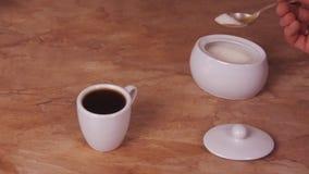 De kop van koffie gegoten suiker De witte kop van hete koffie met toegevoegde suiker Marmeren lijst Wit Sugar Bowl stock videobeelden