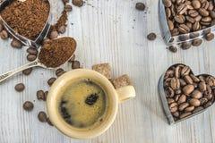 De kop van koffie, de grondkoffie en de koffiebonen in hart vormen  Stock Fotografie