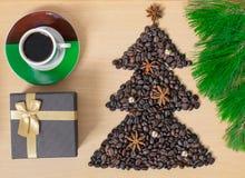 De kop van koffie met Kerstmis stelt en decoratie voor Vorm van Kerstmisboom van koffiebonen wordt gemaakt op houten lijst die royalty-vrije stock afbeelding