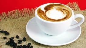 De kop van latte, de cappuccino of de espresso met melk zetten op de rode achtergrond met donkere geroosterde koffiebonen Stock Afbeeldingen