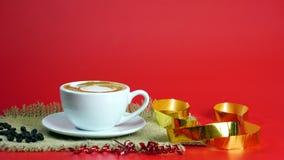 De kop van latte, de cappuccino of de espresso met melk zetten op de rode achtergrond met donkere geroosterde koffiebonen Stock Foto