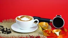 De kop van latte, de cappuccino of de espresso met melk zetten op de rode achtergrond met donkere geroosterde koffiebonen Stock Fotografie