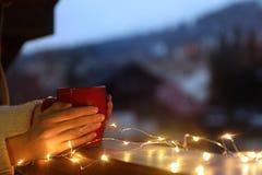 De kop van de vrouwenholding van hete die drank op balkon met Kerstmislichten wordt verfraaid, close-up met ruimte voor tekst royalty-vrije stock afbeeldingen