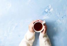 De kop van de vrouwenholding van hete thee op blauwe lijst, dient warme sweater met mok, het concept van de de winterochtend, hoo stock foto's