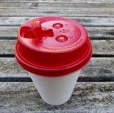 De kop van de Witboekkoffie met rood reisdeksel op houten lijst stock afbeeldingen