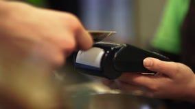 De koper betaalt door de kaart op de betalingsterminal toe te passen en de verkoper geeft een controle uit Close-up stock videobeelden
