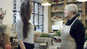 De koper betaalt voor de aankoop door de kaart en de bloemist in zwart sweatshirt geeft aan haar het winkelen zakken stock footage