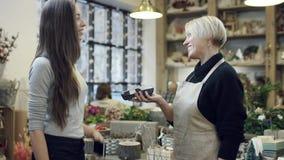 De koper betaalt voor de aankoop door de telefoon aan de bloemist in zwart sweatshirt stock footage