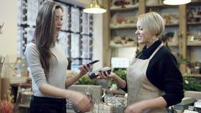 De koper betaalt voor de aankoop door de telefoon en de bloemist in zwart sweatshirt geeft aan haar het winkelen zakken stock footage
