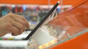 De koper in de elektronikaopslag kiest een nieuw gadget 4k, close-up, onduidelijk beeldachtergrond Het zoeken van een nieuwe vred stock video