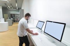 De koper gebruikt een monoblockcomputer in een moderne technologieopslag de mens met een baard kiest een computer bij een opslag stock foto