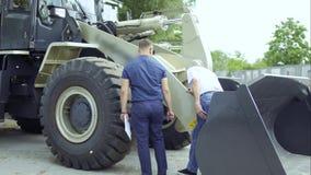 De koper inspecteert in openlucht tractor in toonzaal en spreekt met manager stock video