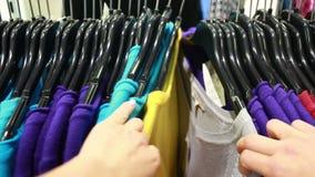 De koper kiest een T-shirt in een boutique stock video