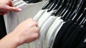 De koper kiest een T-shirt in een boutique stock videobeelden