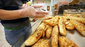 De koper kiest vers brood in een supermarkt stock videobeelden