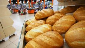 De koper kiest vers brood in een supermarkt stock footage
