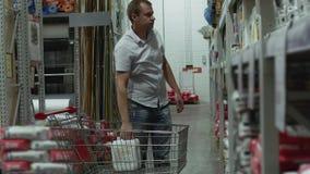 De koper neemt de goederen van de plank en zet hen in het boodschappenwagentje stock videobeelden