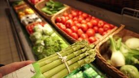 De koper selecteert een bos van verse organische asperge bij de lokale supermarkt stock videobeelden