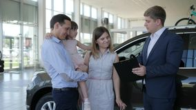 De koper van auto toont duimen, gelukkige familie met autohandelaar in autowinkel, gelukkige professionele cliënt van toonzaal, stock video