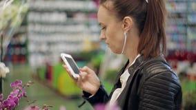 De koper van de meisjesbloem in de supermarkt die met een vriend op de telefoon spreken en kiest huisbloem in een pot stock videobeelden