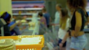 De kopers kiezen salades, het pak van opslagwerknemers stock video