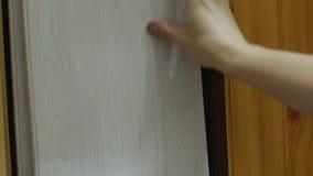De kopers` s handen kiest laminaat in winkel van bouwmaterialen stock video